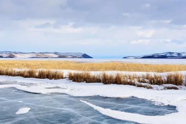 Piękne chmury stratus nad powierzchnią lodu na mroźnym jeziorze z żółtą trawą