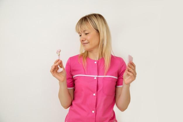 Piękne chwile chińskiego masażu przy użyciu narzędzi kosmetycznych guasha obiecuje pozytywna kosmetolog w różowym ubraniu medycznym. młodość i piękno. salony piękności. zabiegi kosmetyczne. narzędzia kosmetyczki.