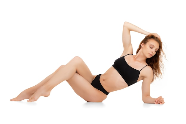 Piękne ciało młodej kaukaskiej kobiety na białej ścianie