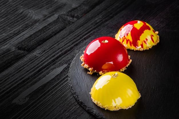 Piękne ciasta pokryte błyszczącą czerwoną i żółtą glazurą koncepcja projektowania deserów cukierniczych
