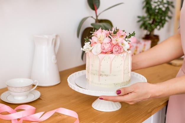 Piękne ciasto z kwiatami na białym stojaku w rękach kobiet