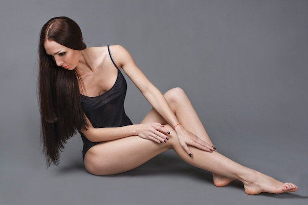 Piękne ciemne włosy dziewczyna z długimi szczupłymi nogami siedzi na szarym tle