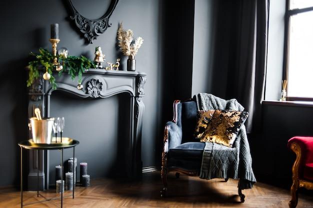 Piękne ciemne wnętrze z fałszywym kominkiem i fotelem