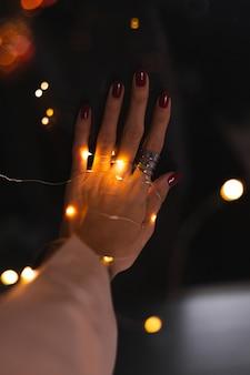 Piękne ciemne zdjęcie kobiecych palców dłoni z dużym srebrnym pierścieniem na kwiatach i świecących światłach