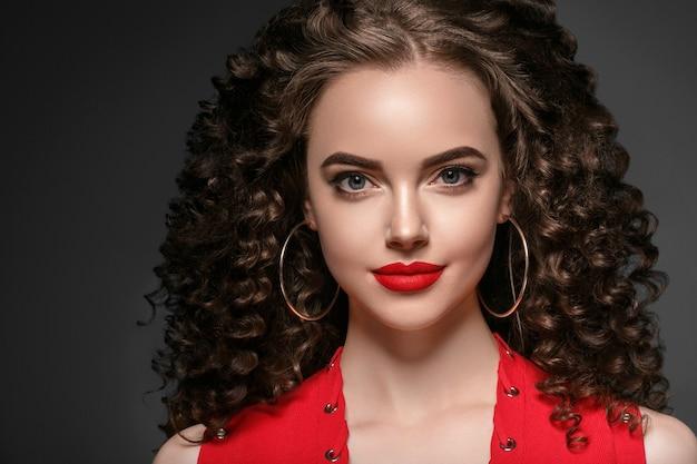 Piękne curly włosy kobieta na czerwono z czerwonymi ustami i manicure sukienka, piękna czerwona fryzura afro. strzał studio.