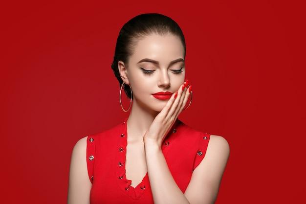Piękne curly włosy kobieta na czerwono z czerwonymi ustami i manicure sukienka, piękna róża fryzura afro na czerwonym tle. strzał studio.