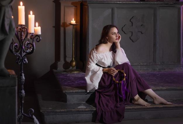Piękne cyganki zbliżenie w ciemnym pokoju kościoła katedralnego z tamburynem muzycznym