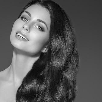 Piękne czarne włosy kobieta portret uroda. niesamowita fryzura kobieca długie kręcone włosy. strzał studio. monochromatyczny szary czarno-biały.