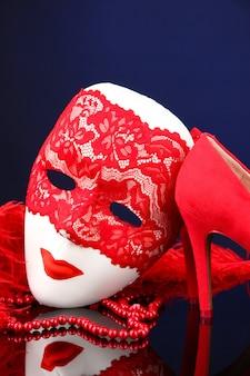 Piękne czerwone buty damskie i karnawałowa maska
