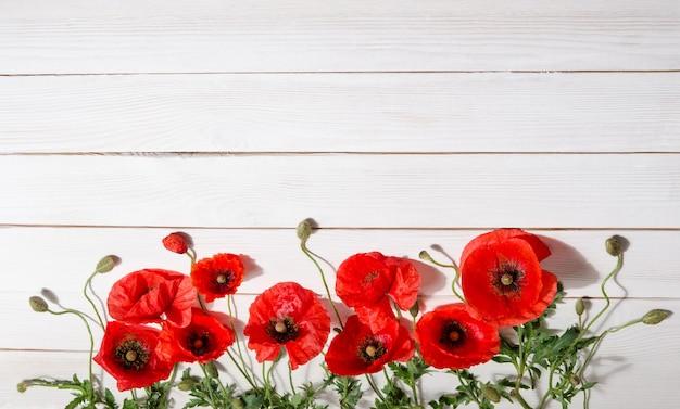 Piękne czerwone maki na starym białym drewnianym stole