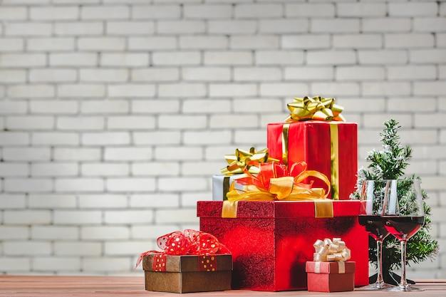 Piękne czerwone pudełka na prezenty i czerwone kieliszki do wina ułożyć na desce drewnianej udekorować małą choinką, niewyraźne białe tło ściany cegła na miejsce.