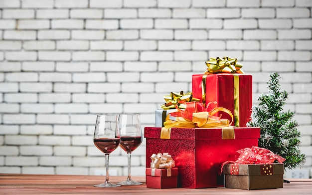 Piękne czerwone pudełka na prezenty i kieliszki do czerwonego wina układają się na desce drewnianej udekorować małą choinką, niewyraźne białe tło ściany cegła dla miejsca kopiowania, układ pionowy.