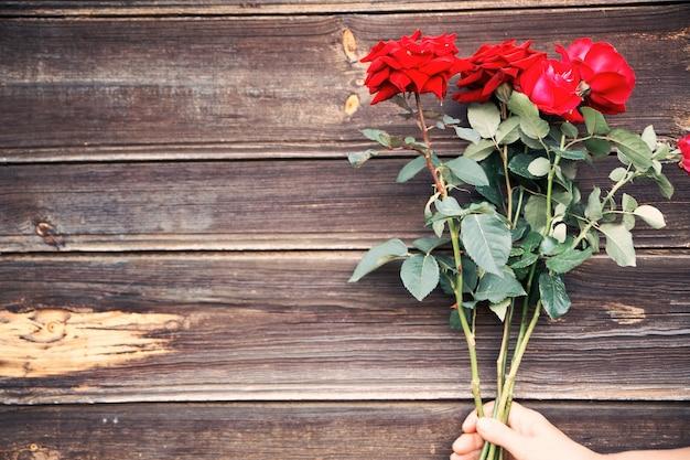 Piękne czerwone róże na drewnie