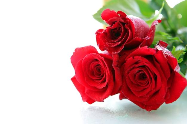 Piękne czerwone róże pojedynczo na białej powierzchni z miejscem na wiadomość.
