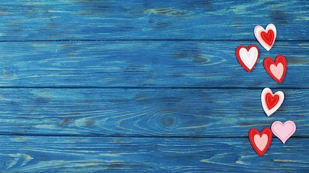 Piękne czerwone serduszka na drewnianym niebieskim tle na walentynki, akcesoria na walentynki, lutowe święto miłości
