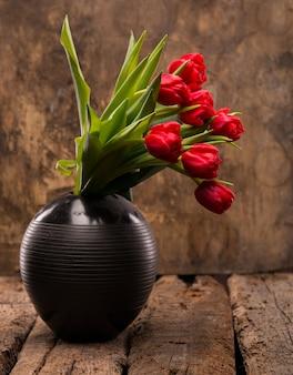 Piękne czerwone tulipany w czarnym wazonie na drewnianym tle