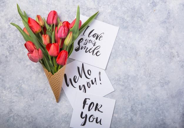 Piękne czerwone tulipany w rożku waflowym lodów z kartą witam na betonowym tle. koncepcyjny pomysł na prezent kwiatowy. wiosenny nastrój