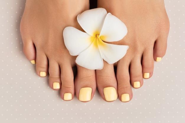 Piękne damskie nogi z letnim wzorem paznokci na powierzchni szarej kropki