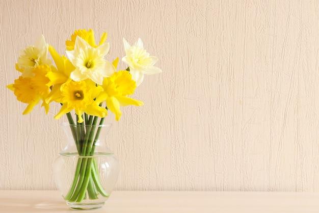 Piękne delikatne żółte żonkile w szklanym wazonie na stole z miejscem na kopię na tle drewna