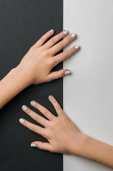 Piękne dłonie dziewczyny ze stylowym makijażem na czarno-białe. dbaj o dłonie.