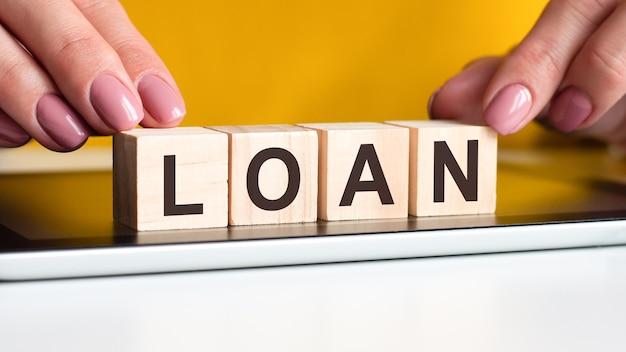 Piękne dłonie kobiety kładą drewniane klocki z literami pożyczki na czarnej powierzchni notesu. może być używany w biznesie, marketingu, edukacji, koncepcji finansowej.