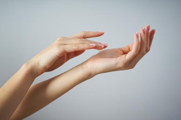 Piękne dłonie młodej dziewczyny z pięknym manicure na szarym tle, koncepcja spa i manicure.
