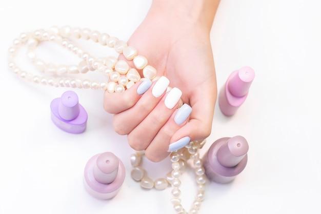 Piękne dłonie młodej kobiety na koralikach z pereł