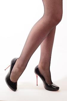 Piękne długie kobiece nogi w bucie na czerwoną szpilkę i rajstopy kabaretki stojąc na białym