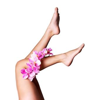 Piękne długie kobiece nogi z kwiatem. koncepcja zabiegów kosmetycznych