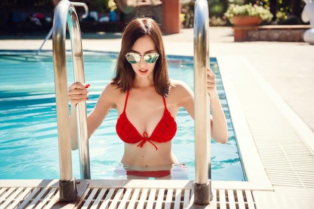 Piękne długie włosy modelki pozowanie przy basenie, portret na zewnątrz. zrelaksować się latem