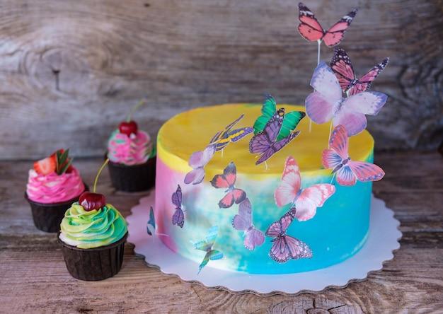 Piękne domowe ciasto niemowlęce z kolorowym kremem maślanym, motylkami waflowymi i babeczkami