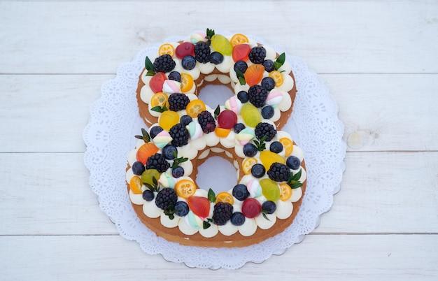 Piękne domowe ciasto w kształcie cyfry osiem z naturalnymi jagodami. tort na międzynarodowy dzień kobiet
