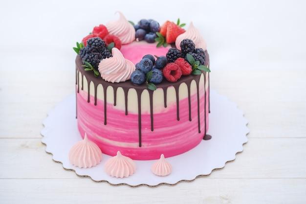 Piękne domowe ciasto z białą śmietaną, polewą czekoladową i naturalnymi świeżymi jagodami na białym stole