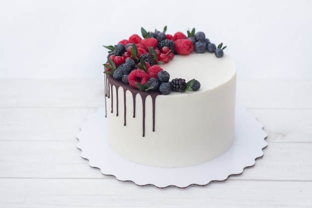 Piękne domowe ciasto z białą śmietaną, polewą czekoladową i naturalnymi świeżymi jagodami