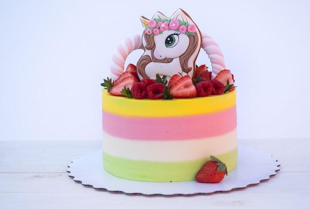 Piękne domowe ciasto z postacią jednorożca, ozdobione świeżymi truskawkami i malinami