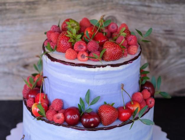 Piękne domowe dwupoziomowe ciasto z kremem serowym fioletowym, ozdobione wiśniami, malinami, truskawkami