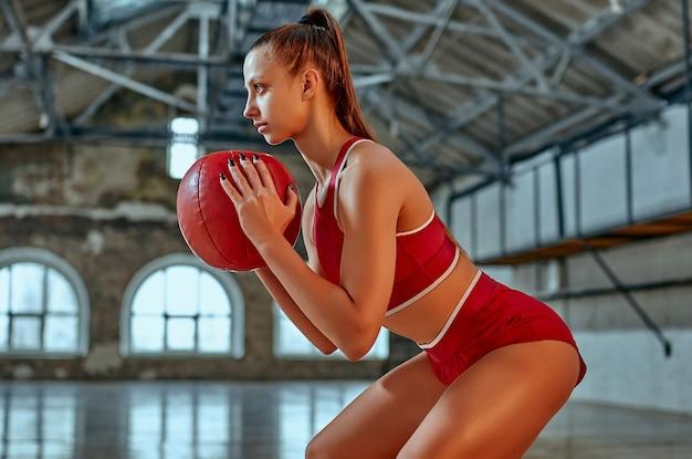 Piękne dopasowanie kaukaski kobieta w odzieży sportowej z funkcjonalną gimnastyką z piłką na siłowni.