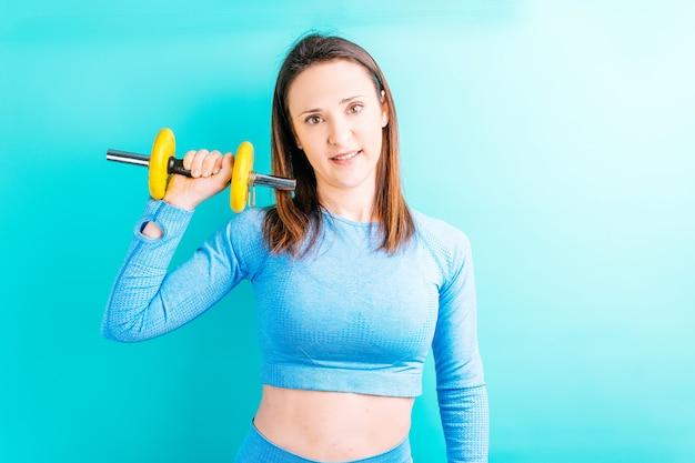 Piękne dopasowanie młoda dorosła kobieta w rajstopach jogi patrząc prosto, trzymając hantle. koncepcja zajęć jogi z miejscem na kopię. ćwiczenia