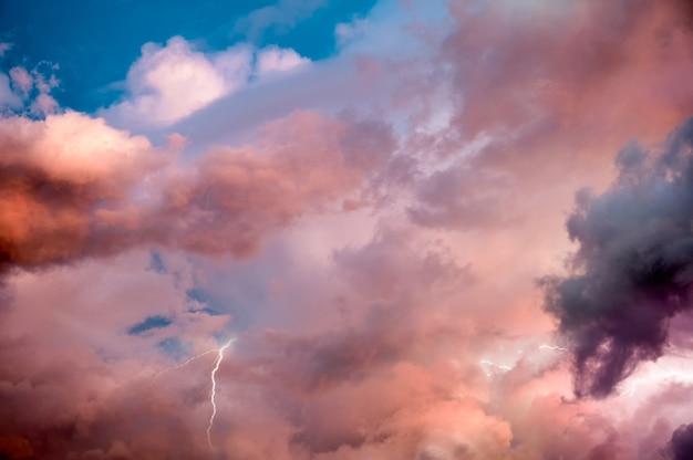Piękne dramatyczne niebo z kolorowymi chmurami i piorunem o zachodzie słońca. naturalne tło