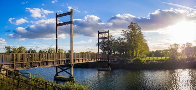 Piękne drzewa w parku z mostem nad rzeką o zachodzie słońca w windsorze w anglii