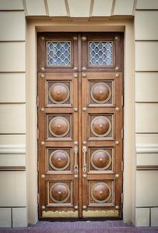 Piękne duże drewniane brązowe drzwi z rzeźbionymi uchwytami