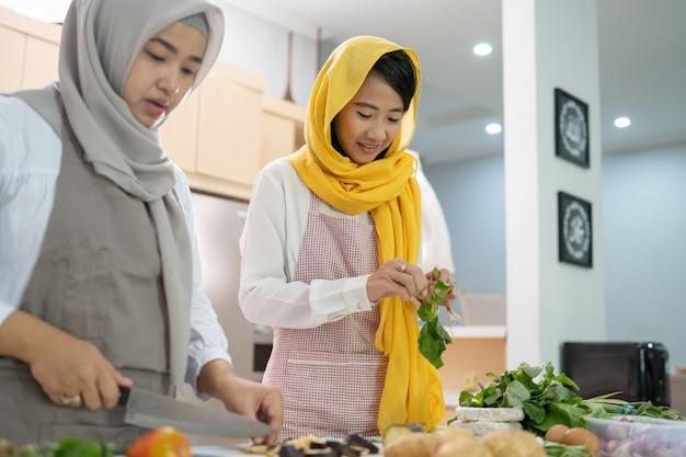 Piękne dwa muzułmańskie kobiety cieszyć się gotowaniem razem obiadu