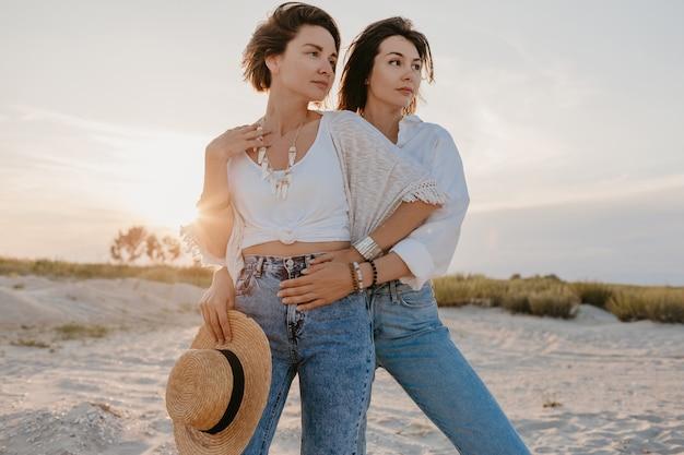 Piękne dwie młode kobiety bawią się na plaży o zachodzie słońca, homoseksualne lesbijki kochają romans