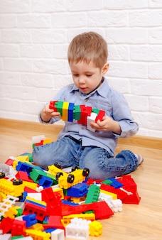 Piękne dzieci bawiące się z konstruktorem na podłodze w domu. dzieci w wieku przedszkolnym zabawy. żłobek, rozwój dzieci. na podłodze kolorowe plastikowe klocki.