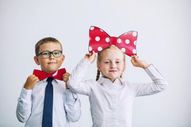 Piękne dzieci chłopiec i dziewczynka z motylami motyli razem w mundurku szkolnym szczęśliwi na białym tle
