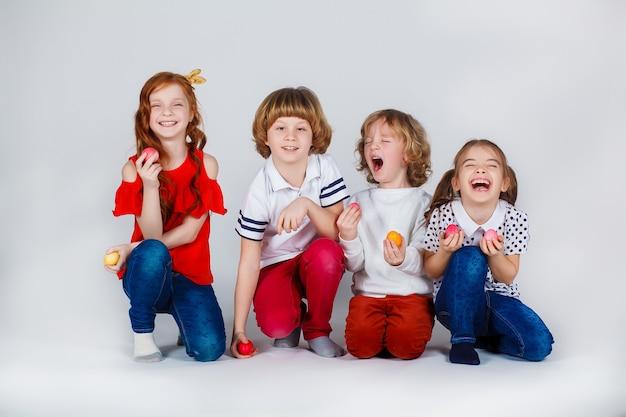 Piękne dzieci stoją z pisankami i dobrze się bawią. śmieszne momenty