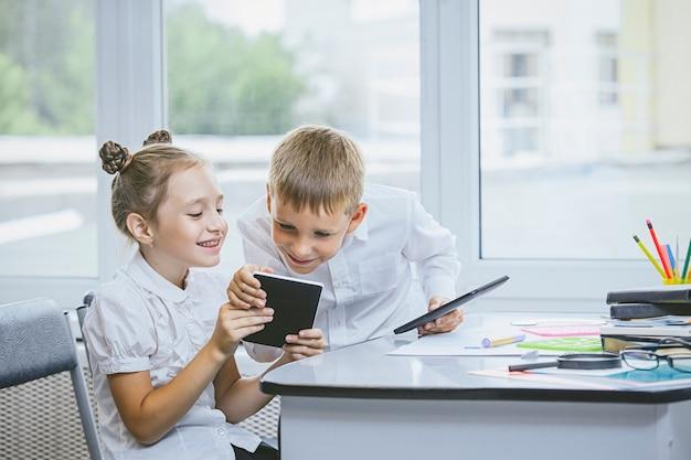 Piękne dzieci to uczniowie razem w klasie w szkole otrzymują edukację za pomocą tabletów szczęśliwi