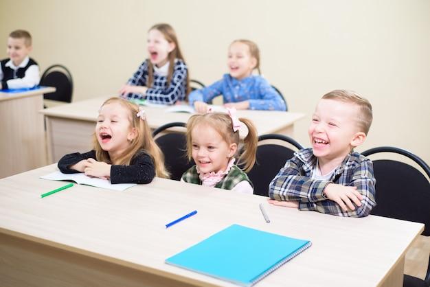 Piękne dzieci uczą się razem w klasie w szkole