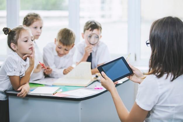 Piękne dzieci, uczniowie i nauczyciel razem w klasie w szkole otrzymują szczęśliwą edukację z tabletami