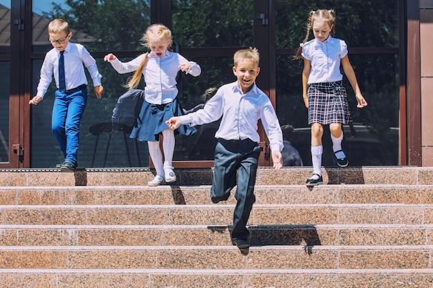 Piękne dzieci w wieku szkolnym aktywne i szczęśliwe na tle szkoły w mundurkach